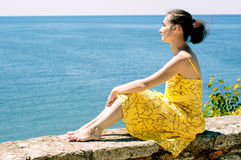 Schöne junge Frau, die das Meer bewundert Lizenzfreies Stockfoto