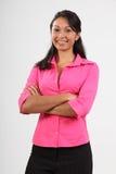Schöne junge Frau, die das rosafarbene Hemdlächeln trägt Stockfoto