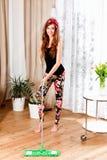 Schöne junge Frau, die das Wohnzimmer aufräumt Stockfotografie