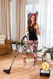 Schöne junge Frau, die das Wohnzimmer säubert Lizenzfreies Stockfoto