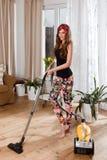 Schöne junge Frau, die das Wohnzimmer säubert Stockbilder