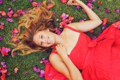 Schöne junge Frau, die in den Blumen liegt lizenzfreies stockbild