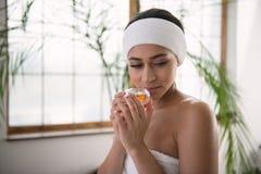Schöne junge Frau, die den Geruch genießt lizenzfreies stockfoto