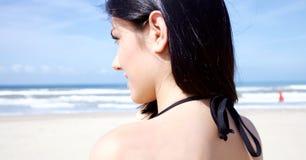 Schöne junge Frau, die den Ozean betrachtet lizenzfreies stockbild