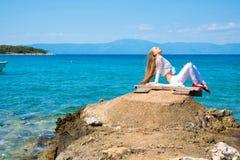Schöne junge Frau, die den Ozean genießt Lizenzfreie Stockfotografie