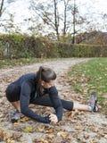 Schöne junge Frau, die in den Park ausdehnt lizenzfreies stockfoto
