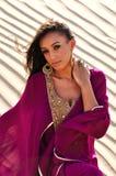 Schöne junge Frau, die in der arabischen Wüste aufwirft Lizenzfreie Stockfotos