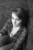 Schöne junge Frau, die in der Ecke sitzt Stockfotografie