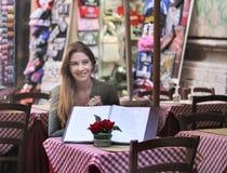 Schöne junge Frau, die in der Gaststätte sitzt Lizenzfreie Stockbilder