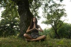 Schöne junge Frau, die in der Natur meditiert Stockfotografie