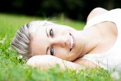 Schöne junge Frau, die in der Natur sich entspannt Lizenzfreie Stockfotos