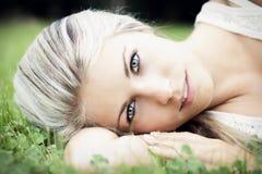 Schöne junge Frau, die in der Natur sich entspannt Stockfotografie