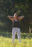 Schöne junge Frau, die in der Natur sich entspannt Stockbilder