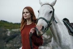 Schöne junge Frau, die in die Berge mit ihrem Pferd geht Stockbild