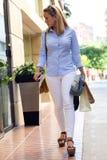 Schöne junge Frau, die in die Straße geht Fahrwerkbeine und Frauenbeutel auf weißem Hintergrund Lizenzfreies Stockbild