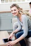 Schöne junge Frau, die digitale Tablette verwendet Stockbilder
