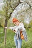 Schöne junge Frau, die draußen auf einem Gebiet, ihren Handy betrachtend geht stockbilder