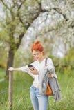 Schöne junge Frau, die draußen auf einem Gebiet, ihren Handy betrachtend geht lizenzfreies stockfoto