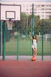 Schöne junge Frau, die draußen Basketball spielt stockfoto