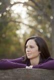 Schöne junge Frau, die draußen denkt stockfotografie