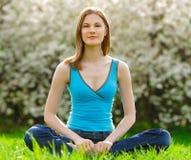 Schöne junge Frau, die draußen meditiert Lizenzfreie Stockbilder