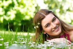 Schöne junge Frau, die draußen mit Blumen lächelt Lizenzfreie Stockfotos