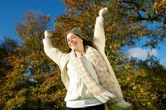 Schöne junge Frau, die draußen mit den Armen ausgestreckt lächelt Stockfotografie