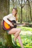 Schöne junge Frau, die draußen mit Gitarre lächelt Stockfotos
