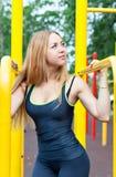 Schöne junge Frau, die draußen Training auf den Stangen ausübt Stockbilder