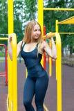 Schöne junge Frau, die draußen Training auf den Stangen ausübt Lizenzfreie Stockfotos