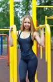 Schöne junge Frau, die draußen Training auf den Stangen ausübt Lizenzfreies Stockbild