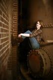 Schöne junge Frau, die durch Boiler sitzt Stockbilder