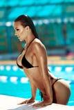 Schöne junge Frau, die durch das Pool aufwirft Lizenzfreies Stockbild