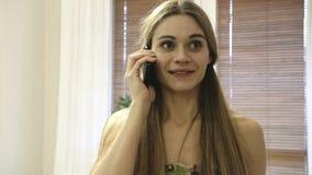Schöne junge Frau, die durch den Handy und die Verschlechterungsnachrichten spricht stock footage