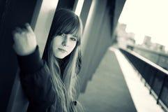 Schöne junge Frau, die durch die Wand aufwirft lizenzfreie stockfotos