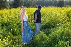 Schöne junge Frau, die durch ein Feld geführt wird Stockfotografie