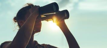 Schöne junge Frau, die durch Ferngläser dem Meer auf A betrachtet lizenzfreie stockfotos