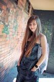 Schöne junge Frau, die durch Graffitiwand aufwirft stockfotos
