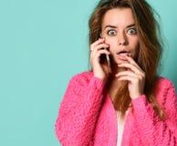 Schöne junge Frau, die durch Handy auf hellem Hintergrund spricht stockbild