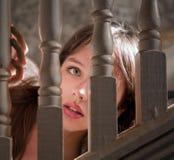 Schöne junge Frau, die durch Treppenhaus späht Lizenzfreie Stockfotos