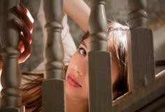 Schöne junge Frau, die durch Treppenhaus späht Stockbild