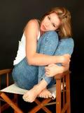 Schöne junge Frau, die durchdacht in einem Stuhl sitzt Lizenzfreie Stockfotografie