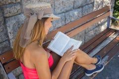 Schöne junge Frau, die ein Buch auf einer Bank liest lizenzfreie stockfotos
