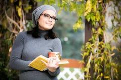 Schöne junge Frau, die ein Buch liest und Tee trinkt Lizenzfreie Stockfotografie