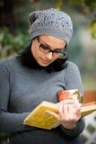 Schöne junge Frau, die ein Buch liest und Tee trinkt Lizenzfreies Stockbild