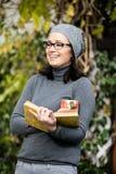 Schöne junge Frau, die ein Buch liest und Tee trinkt Lizenzfreie Stockbilder
