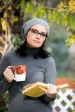 Schöne junge Frau, die ein Buch liest und Tee trinkt Lizenzfreie Stockfotos