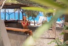 Schöne junge Frau, die ein Cocktail an einer Strandbar genießt lizenzfreie stockbilder