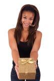 Schöne junge Frau, die ein Geschenk, getrennt auf Weiß anhält Lizenzfreie Stockfotos