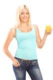 Schöne junge Frau, die ein Glas Orangensaft und posin hält Lizenzfreies Stockbild